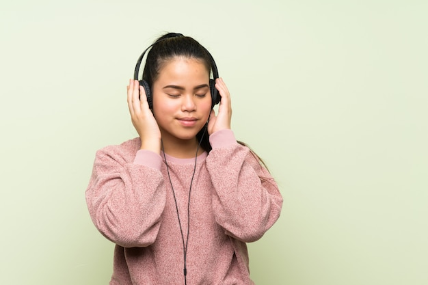 Młodego nastolatka azjatycka dziewczyna nad odosobnioną zieleni ścianą słucha muzyka z hełmofonami
