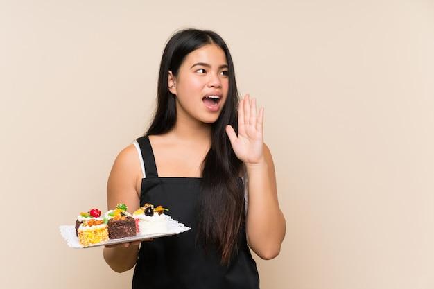 Młodego nastolatka azjatycka dziewczyna trzyma mnóstwo różne mini torty nad odosobnioną ścianą krzyczy z szeroko otwarty usta