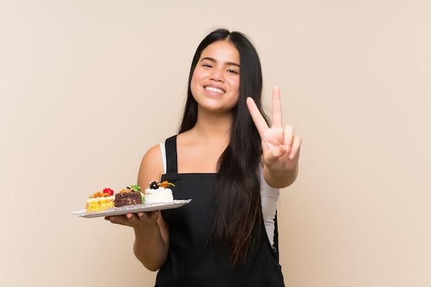 Młodego nastolatka azjatycka dziewczyna trzyma mnóstwo różnych mini torty nad odosobnionym tłem uśmiecha się znak zwycięstwa i pokazuje