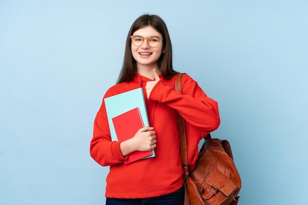 Młodego nastolatka studencka dziewczyna trzyma książki nad błękit ścianą daje aprobata gestowi