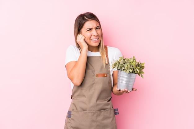 Młodego ogrodnika caucasian kobiety nakrywkowi ucho z rękami.