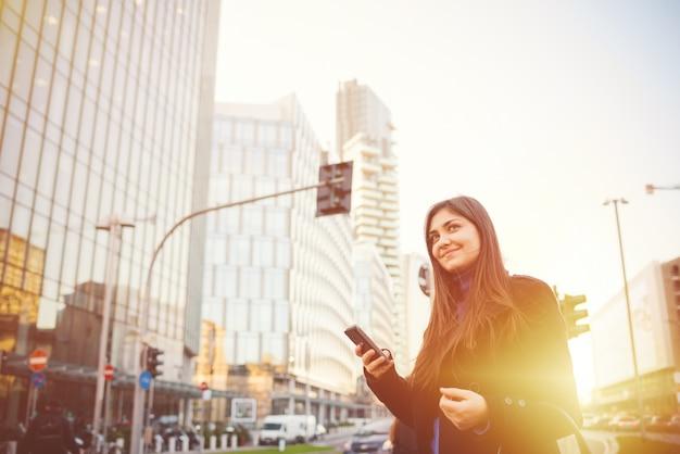 Młodego pięknego bizneswomanu plenerowy backlight używać smartphone
