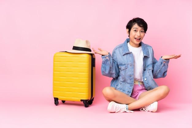 Młodego podróżnika wietnamska kobieta z walizki obsiadaniem na podłoga