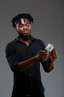 Młodego pomyślnego afrykańskiego biznesmena płonący pieniądze na zmroku