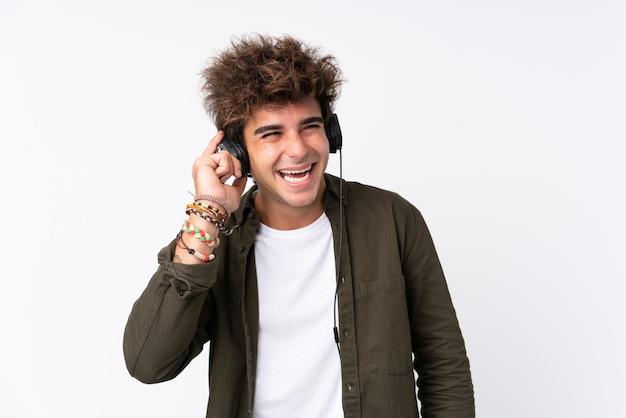 Młodego przystojnego mężczyzna słuchająca muzyka nad odosobnioną biel ścianą