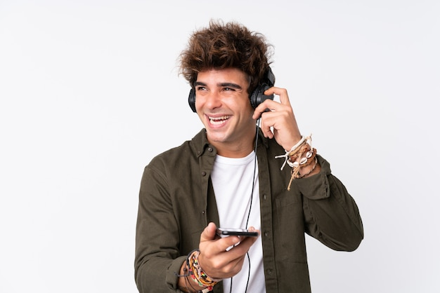 Młodego przystojnego mężczyzna słuchająca muzyka z wiszącą ozdobą nad odosobnioną biel ścianą