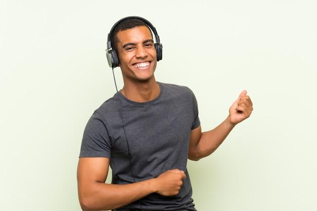 Młodego przystojnego mężczyzna słuchająca muzyka z wiszącą ozdobą nad odosobnioną zieleni ścianą