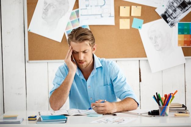 Młodego przystojnego ufnego zadumanego biznesmena pracujący obsiadanie przy stołowym główkowaniem nad notepad. białe nowoczesne wnętrze biura