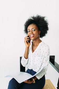 Młodego uśmiechniętego amerykanina afrykańskiego pochodzenia biznesowa kobieta używa telefon, odosobnionego na bielu