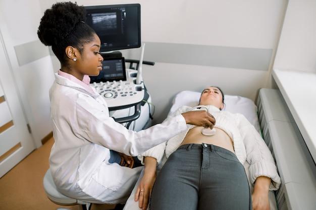 Młodej afrykańskiej kobiety lekarki ultradźwiękowy poruszający przetwornik na kobieta brzuchu w szpitalu