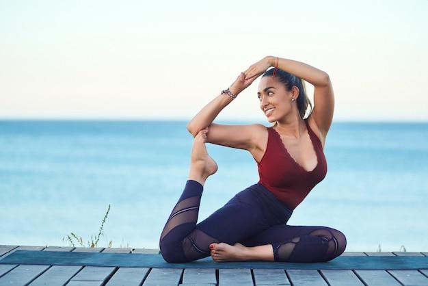 Młodej atrakcyjnej kobiety ćwiczy joga na plaży przy zmierzchem.