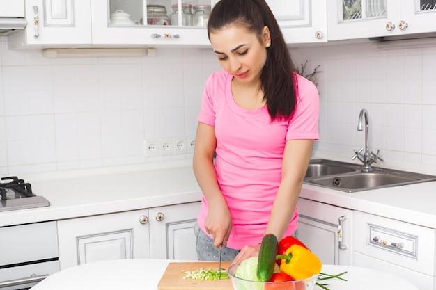 Młodej atrakcyjnej kobiety kulinarna sałatka indoors przy kuchnią