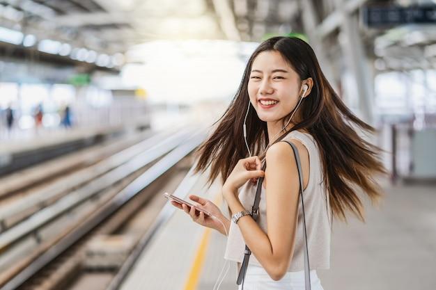 Młodej azjatyckiej kobiety pasażerska słuchająca muzyka