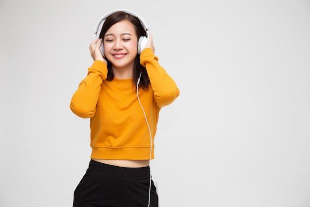 Młodej azjatyckiej piękno kobiety słuchająca muzyka z hełmofonami w listy odtwarzania pieśniowym zastosowaniu na smartphone odizolowywającym