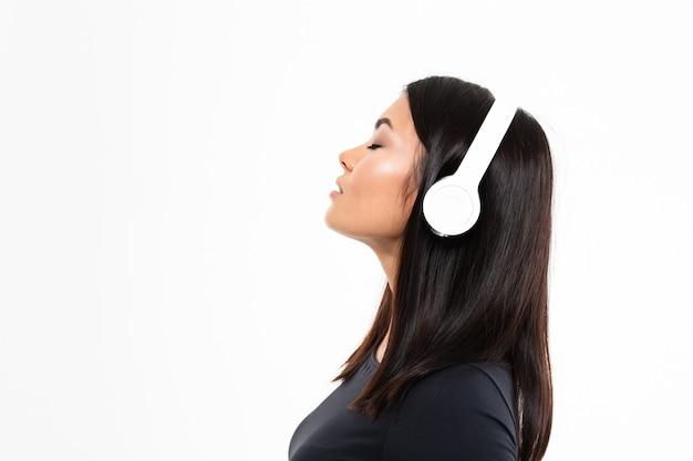 Młodej azjatykciej damy słuchająca muzyka z hełmofonami
