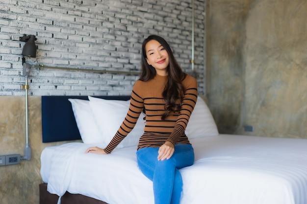 Młodej azjatykciej kobiety szczęśliwy uśmiech relaksuje na łóżku w sypialni