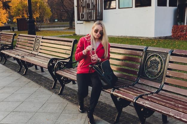 Młodej blondynki biznesowa kobieta z torbą w parku.