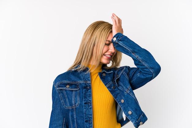 Młodej blondynki caucasian kobieta odizolowywał zapominać coś, uderzać czoło dłonią i zamykać oczy.