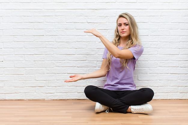 Młodej blondynki ładna kobieta trzyma przedmiot obiema rękami na stronie kopii przestrzeni, pokazuje, oferuje lub reklamuje przedmiot