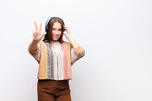 Młodej blondynki ładnej dziewczyny słuchająca muzyka z hełmofony przeciw biel ścianie