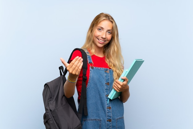Młodej blondynki studencka kobieta nad odosobnioną błękit ścianą zaprasza przychodzić