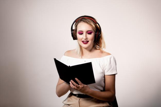 Młodej blondynki żeński operator w hełmofonach z notatnikiem na lekkim tle. makieta