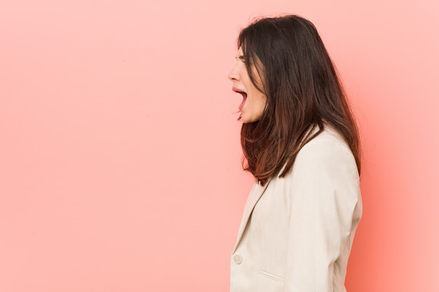 Młodej brunetki biznesowa kobieta krzyczy w kierunku odbitkowej przestrzeni przeciw różowej ścianie