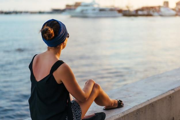 Młodej brunetki turystycznej dziewczyny relaksujący pobliski morze