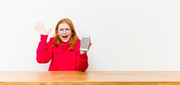 Młodej czerwieni głowy ładna kobieta przed drewnianym stołem z telefonem komórkowym