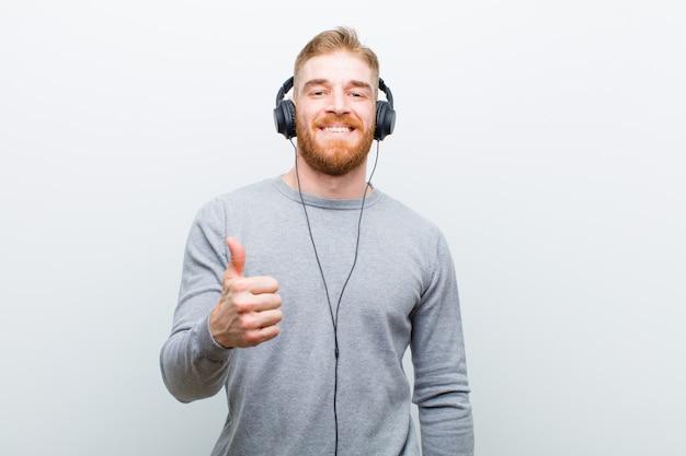 Młodej czerwieni głowy mężczyzna słuchająca muzyka z hełmofonami przeciw białemu tłu