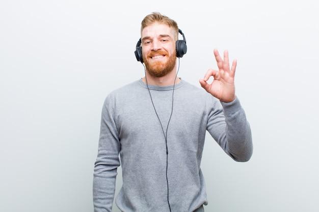 Młodej czerwieni głowy mężczyzna słuchająca muzyka z hełmofonami przeciw bielowi