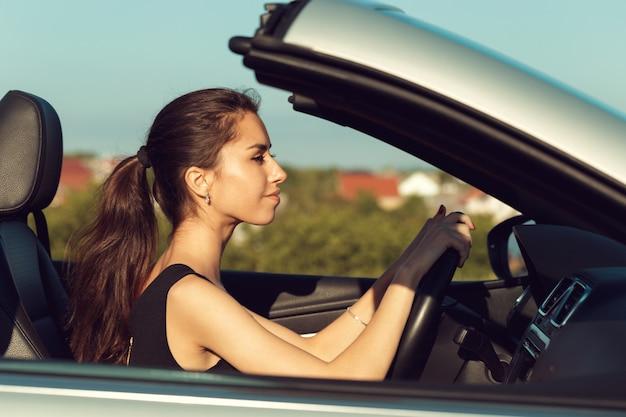 Młodej dziewczyny cabrio napędowy samochód na zmierzchu świetle