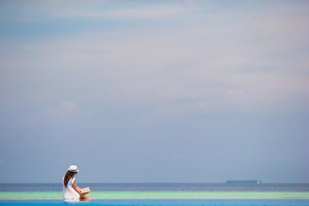 Młodej dziewczyny czytelnicza książka blisko pływackiego basenu