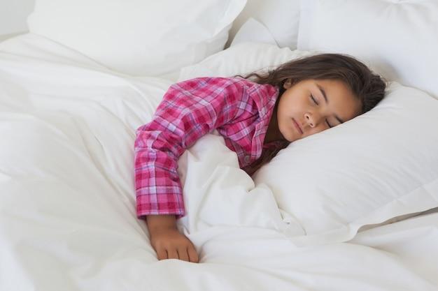Młodej dziewczyny dosypianie w łóżku w domu