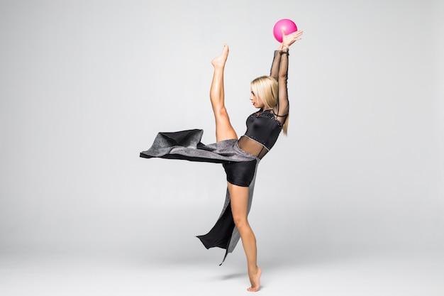 Młodej dziewczyny gimnastyczki obsiadanie z piłką odizolowywającą