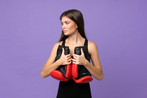 Młodej dziewczyny kobieta nad odosobnionym tłem z bokserskimi rękawiczkami
