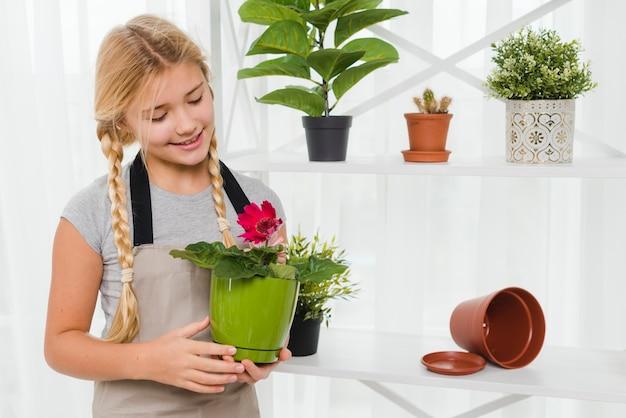 Młodej dziewczyny mienia kwiatów garnek