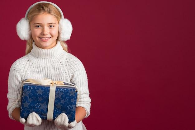 Młodej dziewczyny mienia prezenta kopii przestrzeń