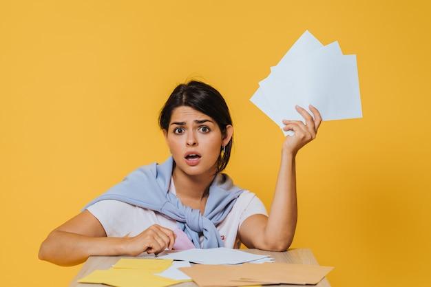 Młodej dziewczyny oszołomienie trzyma kilka koperty i siedzi na żółtym tle przy stołem