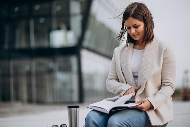 Młodej dziewczyny siedząca czytelnicza książka i pić kawa na zewnątrz ulicy