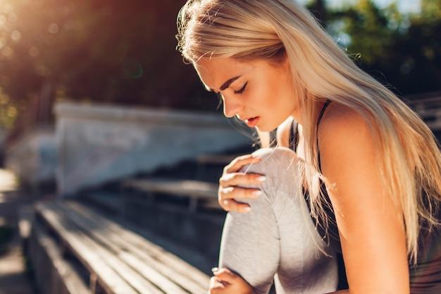 Młodej kobiety atleta dotyka jej kolano po biegać na sportsground