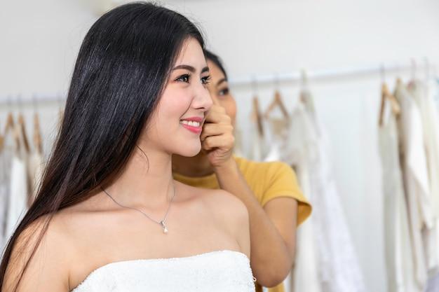 Młodej kobiety azjatycki ono uśmiecha się i próbuje na ślubnej sukni w sklepie.