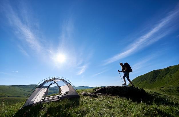 Młodej kobiety backpacker z plecakiem i trekkingowymi kijami wspina się up na dużym kamieniu na szczycie wzgórza blisko namiotu przeciw niebieskiemu niebu, słońcu i chmurom, w górach. koncepcja kempingowego stylu życia