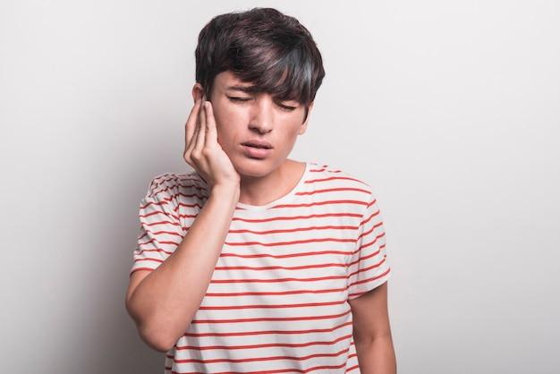 Młodej kobiety cierpienie od toothache przeciw białemu tłu