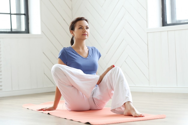 Młodej kobiety ćwiczy joga na joga macie