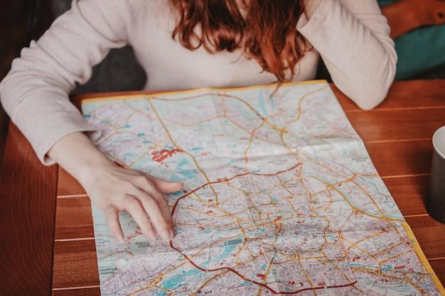 Młodej kobiety czerwieni głowy dziewczyny podróżnik czyta patrzejący papierową mapę w kawiarni