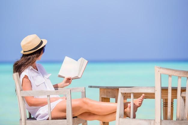 Młodej kobiety czytanie przy plenerową plażową kawiarnią