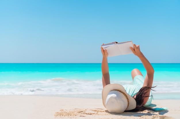 Młodej kobiety czytelnicza książka kłama tropikalną biel plażę