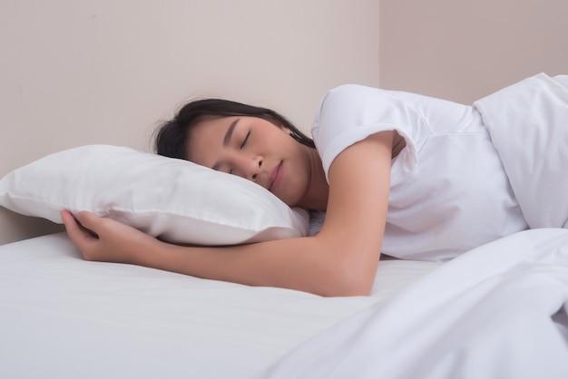 Młodej kobiety dosypianie w jej łóżku