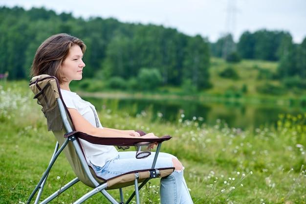 Młodej kobiety freelancer siedzi na krześle i relaksuje w naturze blisko jeziora. aktywność na świeżym powietrzu w lecie. przygoda w parku narodowym. wypoczynek, wakacje, relaks